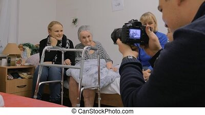 Family visiting elderly grandmother and taking photo with her