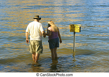 Family Wading - Father protectively steadies daughter while...