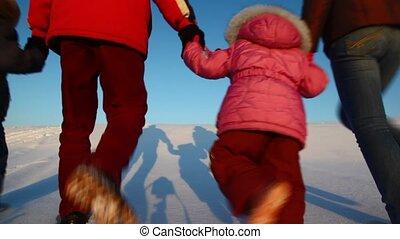 family walk behind on snow hill on sundown