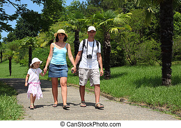 family walk on road in Sochi arboretum