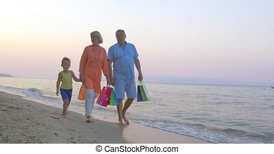 Family walk on the beach after shopping