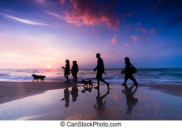 Family walk on the beach at sunset
