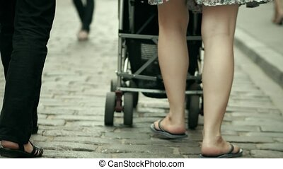 Family walk with the baby stroller on cobblestone pavement