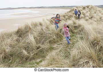 Family Walking Along Dunes On Winter Beach