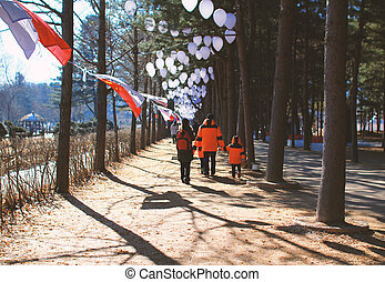 Family walking at park in winter.