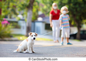 Family walking dog during virus outbreak. Woman and child wearing face mask in coronavirus lockdown and quarantine. Home animal and pet. Mother and child with puppy in pandemic or air pollution.