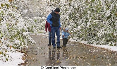 family walking in a snowy alley in the autumn Park