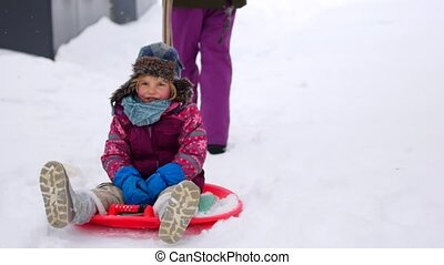 Family walking in a winter park. Parents with child on sled