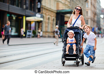 Family walking in city center - Young mother with her son...