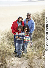 Family Walking In Dunes On Winter Beach
