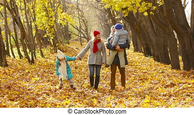 Family Walking in Park - Family of four approaching camera...