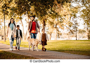 Family walking in park with dog