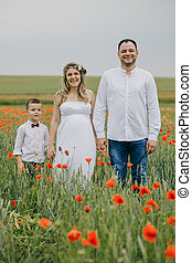 Family walking in poppy field holding hands