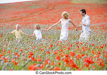 Family walking in poppy field holding hands smiling