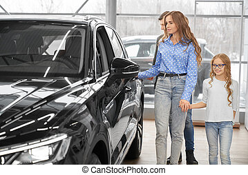 Family walking in showroom of dealership, observing auto.