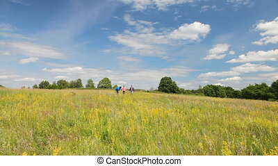 Family walking in the summer field