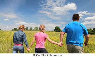 Family walking in the summer field