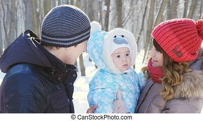 Family walking in the winter park in slowmotion