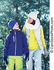 Family walking in winter day, happy mother and child son dressed in bright sportswear have fun together over christmas tree