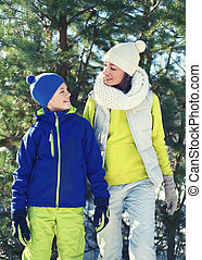 Family walking in winter day, happy young mother and child dress