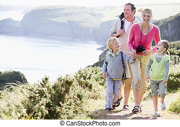 Family walking on cliffside path holding hands and smiling