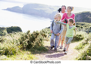 Family walking on cliffside path pointing and smiling