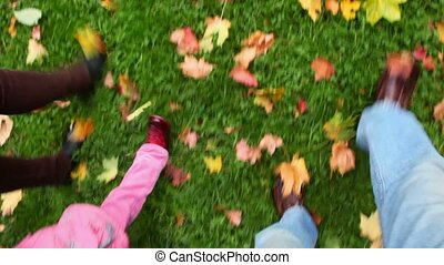 family walking on green grass with autumn leaves, view to foots