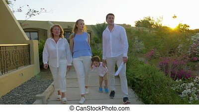 Family walking on resort area in the evening