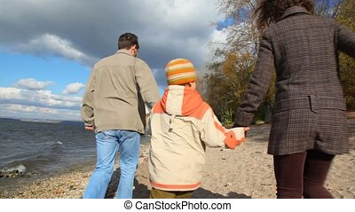 family walking on sandy bank of river