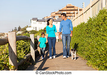 family walking their dog at the beach