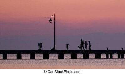 Family walking their dog on a pier at sunset - Family...