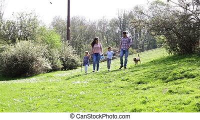 Family Walking their Dog - Family of four are walking their...