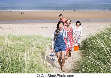 Family walking up sand dunes
