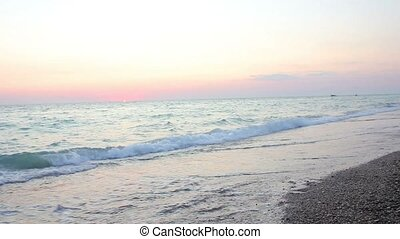 Family walks on the beach at sunset