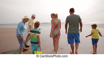 Family Walks on the Beach - Slow motion, tracking shot, of a...