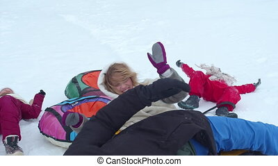Family wallowing in the snow and having fun