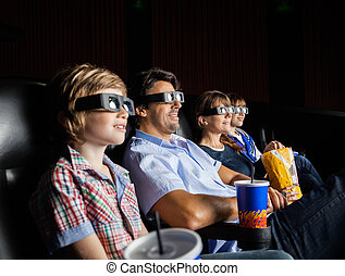 Family Watching 3D Movie In Theater - Family with snacks...