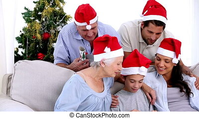 Family watching little boy open chr