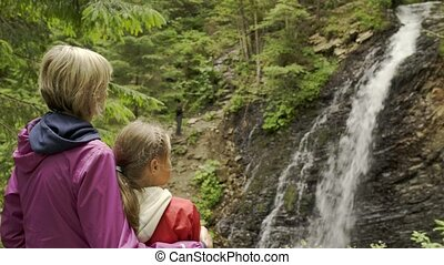 Family watching mountain waterfall - Mouther and a child...