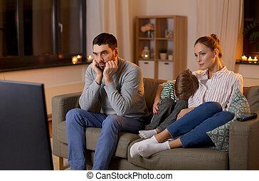 family watching something boring on tv at night