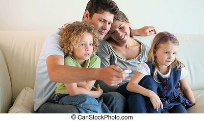 Family watching televison while sitting on a sofa