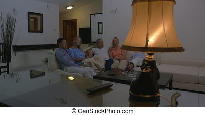 Family watching TV at home in the evening