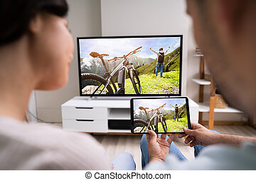 Family Watching TV Through Tablet Streaming Television