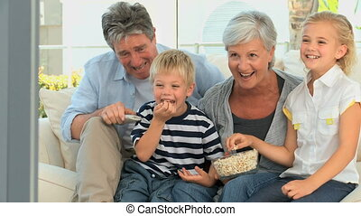 Family watching tv while eating popcorn