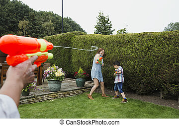 Family Water Fight in the Garden