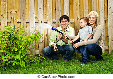 Family watering plant - Happy family in backyard watering...