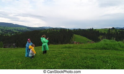 Family wearing raincoats while walking in meadow and making...