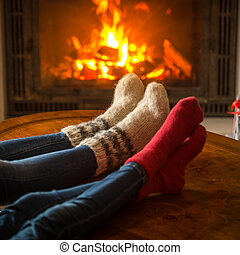 Family wearing socks sitting in chalet by burning fireplace