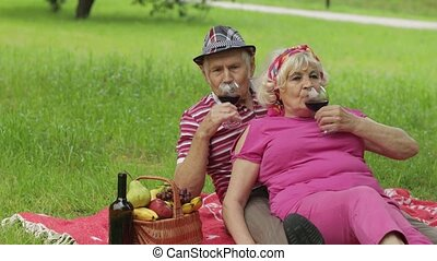 Family weekend picnic in park. Old people, active senior caucasian couple sit on blanket and drink wine. Talking and celebrating anniversary. Elderly man, woman. Husband, wife. Grandpa, grandma