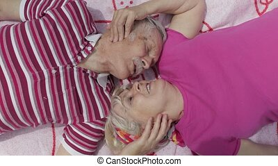 Family happy weekend picnic. Old people, active senior caucasian couple lie on blanket facing each other. Talking and making a kiss. Elderly man, woman. Celebrating anniversary date. Grandparents